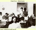 Aula em Angicos, em 1963: 300 pessoas alfabetizadas pelo método Paulo Freire em um mês. O ambiente político-cultural em que Paulo Freire elaborou suas idéias e começou a experimentá-las na prática foi o mesmo que formou outros intelectuais de primeira linha, como o economista Celso Furtado e o antropólogo Darcy Ribeiro (1922-1997).  Todos eles despertaram intelectualmente para o Brasil no período iniciado pela revolução de 1930 e terminado com o golpe militar de 1964. A primeira data marca a retirada de cena da oligarquia cafeeira e a segunda, uma reação de força às contradições criadas por conflitos de interesses entre grandes grupos da sociedade. Durante esse intervalo de três décadas ocorreu uma mobilização inédita dos chamados setores populares, com o apoio engajado da maior parte da intelectualidade brasileira. Especialmente importante nesse processo foi a ação de grupos da Igreja Católica, uma inspiração que já marcara Freire desde casa (por influência da mãe).  O Plano Nacional de Alfabetização do governo João Goulart, assumido pelo educador, se inseria no projeto populista do presidente e encontrava no Nordeste – onde metade da população de 30 milhões era analfabeta – um cenário de organização social crescente, exemplificado pela atuação das Ligas Camponesas em favor da reforma agrária. No exílio e, depois, de volta ao Brasil, Freire faria uma reflexão crítica sobre o período, tentando incorporá-la a sua teoria pedagógica. Foto: acervo fotográfico dos arquivos de Paulo Freire - Instituto Paulo Freire