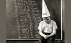 """Foto antiga de um menino deixado de castigo, com um chapéu de burro sobre a cabeça, depois de ter escrito várias vezes no quadro: """"Eu serei bom""""."""