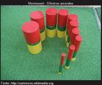 Cilindros coloridos dispostos em espiral, que variam em altura e largura. A menor cilindro é o mais fino e mais alto do cilindro é o mais grosso.