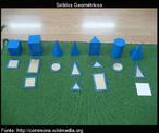 Dez Formas geométricas tridimensionais feitos de madeira e geralmente pintados de azul. As formas são: esfera, cone, elispóide, triângulo, cubo, cilindro, prisma retangular, prisma triangular.